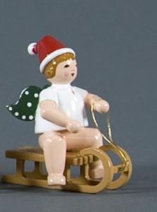 Weihnachtsengel auf Schlitten sitzend mit Mütze